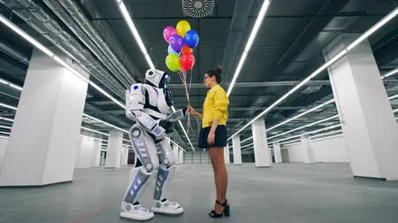 bot : Woman gives balloons as a present to her friend droid. Stock Footage