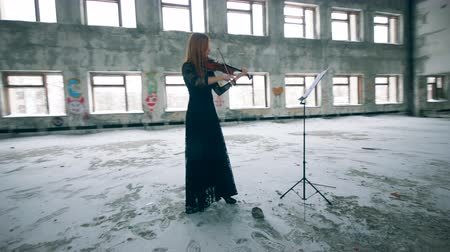 concert hall : Woman in a dress in playing the violin in an unkempt hall Stock Footage
