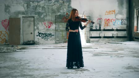 cellist : Abandoned building with a female violinist playing the instrument