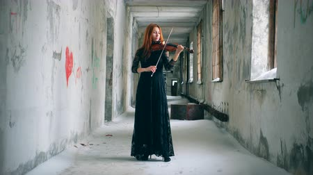 orchestre : Rundown corridor with a redhead woman playing the violin Vidéos Libres De Droits