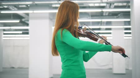 concertgebouw : Redhead woman is skillfully playing the violin in an empty hall