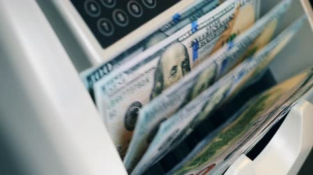 mennyiség : Dollar banknotes are moving inside of a counting device Stock mozgókép