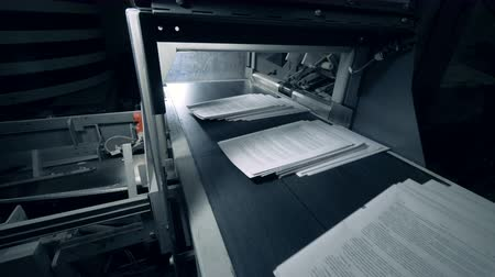 публиковать : White sheets of paper moving on a typographic conveyor, automated machine.