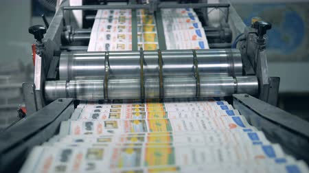 публиковать : Many newspaper moving on a conveyor in a printing facility.