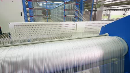 spool : Factory loom weaves white fiber in a facility room.