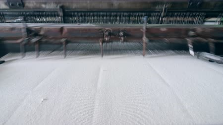 clothes line : Automated machine weaves fabric in a textile facility.