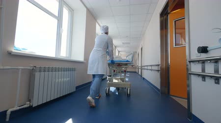 karetka : Doctors are riding an ambulance cart through the corridor