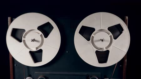 gravador : Zoom-in of a tape recorder with spinning reels
