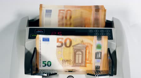 összeg : A stack of euro banknotes is getting counted mechanically