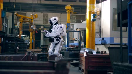 droid : Human-like cyborg is using a tablet in factory premises Stock Footage