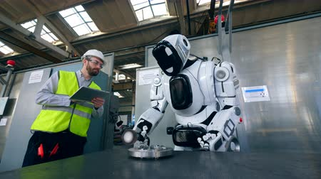 lavorazioni meccaniche : Cyborg is processing metal with a worker standing near