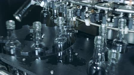unfilled : Glass bottles are moving around metal conveyors