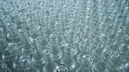 unfilled : Glass bottles stacked together on a moving platform