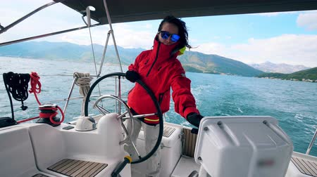 kapitán : Yacht is sailing across water while being controlled by a lady