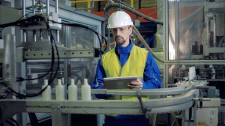 gyógyszertár : Male engineer is inspecting production of plastic containers