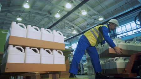 polymers : Industrial worker is stacking carton trays with plastic canisters