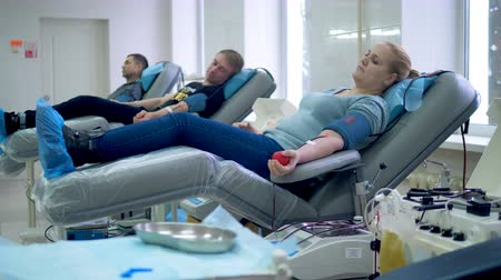 pacientes : People are donating blood while lying in medical armchairs
