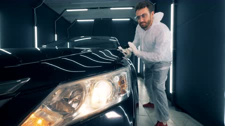 detailing : Male specialist is using a cloth to glaze a car Stock Footage
