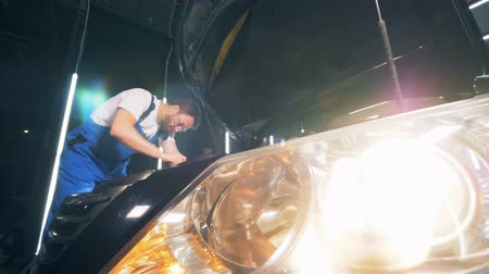 固定 : Switched on headlight of a car which is being fixed by a man