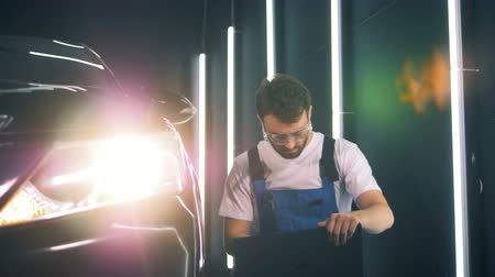 detailing : Male engineer is inspecting an automobile with his laptop