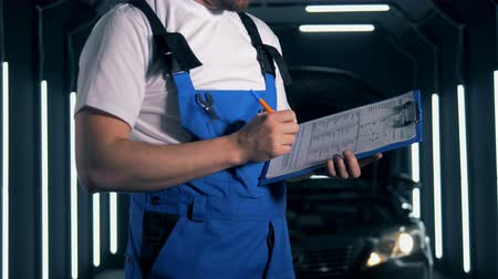 polido : Male engineer is writing a report after inspecting a car. Car service concept.