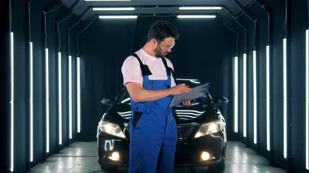 ladění : Car service concept. Car-care with male technician writing a report