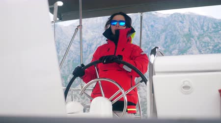 A woman wearing an anorak is navigating a yacht