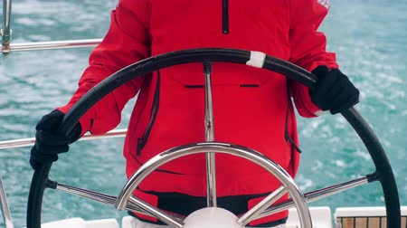 A person in a red parka is holding the wheel of a boat
