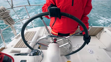 skillful : Boats steering wheel is being navigated by the professional