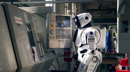 White droid pushes buttons on a machine at a factory.