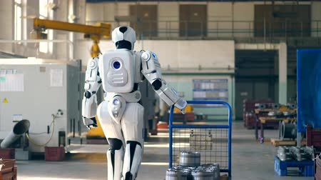 mecânica : Bionic robot pulls a cart, walking in a factory room.