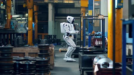 droid : Bionic droid walks in a factory room and types on a tablet. Stock Footage
