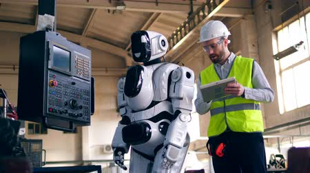 Person checks working robot, standing in a factory room. Stock mozgókép