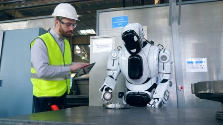One man types on a tablet while a cyborg works with a factory detail.