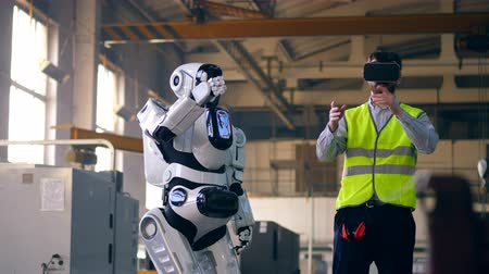 An engineer uses VR equipment to control a droid at a factory. Stock mozgókép