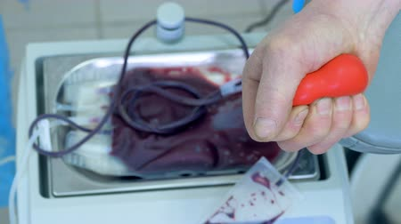 пожертвование : Blood donation concept. Male fingers are squeezing a rubber heart whit donating blood