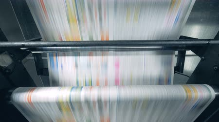 nakladatelství : Printed newspaper rolling on a conveyor, typographical equipment works.