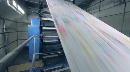 Long paper sheets moving on a line at a print office, factory equipment in work.