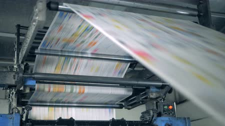 публиковать : A machine works, rolling printed newspaper in typography facility.