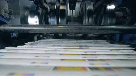 Stacks of printed newspaper on a conveyor, print office equipment. Stock mozgókép