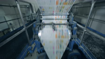 Colored newspaper sheets moving on a typography conveyor, printing office.