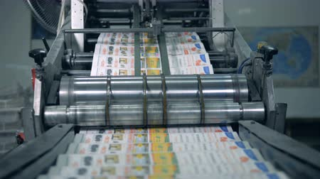 nakladatelství : Printed newspaper moving on a typography line, automatic production.