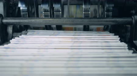 Stacked newspaper on automated conveyor, typography facility. Stock mozgókép