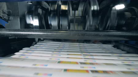 Print office machines moving newspaper on automated line.