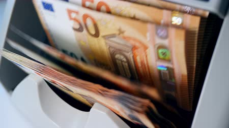 Euro banknotes are getting calculated on a machine