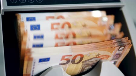 Euro bills are getting calculated inside of a machine