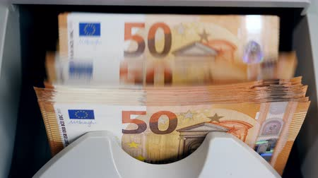 Fifty-euro bills are being processed by counting equipment