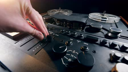 reproduktory : Person turns on a tape recorder with rotating bobbins.