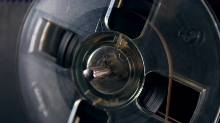 cassette : A plastic spool with tape rotates on a music player. Stock Footage
