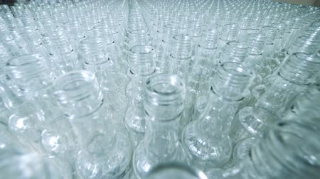Plenty of glass bottles on a conveyor, alcoholic production.